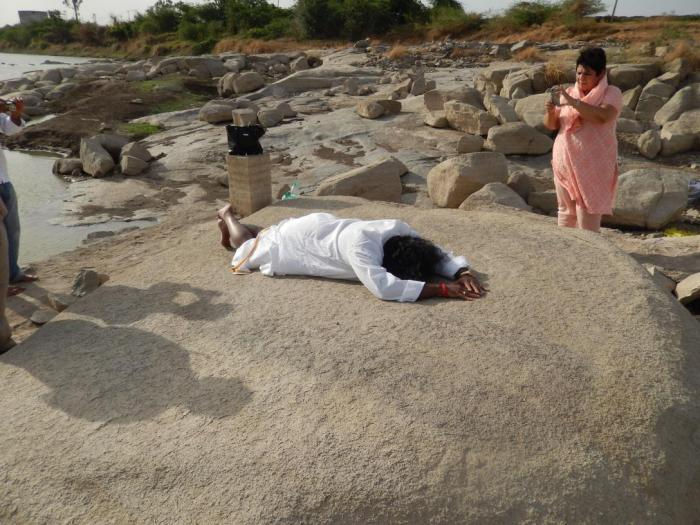 "Mohanji Prostrating to SriPada Sri Vallabhab ""on the rock"" which was used by SriPada Sri Valabha to do SuryaNamaskar every morning. It is said that that such was the 'Tej' of Sri Pada, Sri Valabha that the color of the rock darkened. In this picture Preeti is also clicking another one."