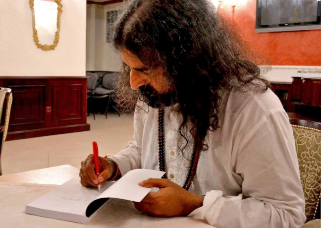 7 Mohanji taking time to sign each Power of Purity book with love