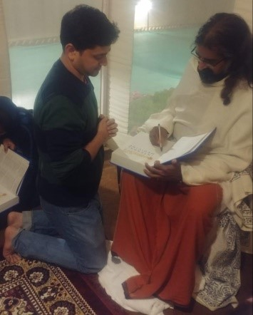 Mohanji Chronicles Blog - A Dip At The Kumbh Mela - Freedom From A Bond - Mohanji signing Pritam's medicine study book